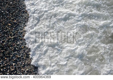 White Foamy Wave Crashing On Pebble Beach