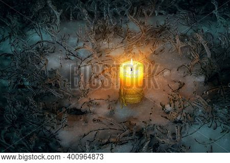 Christmas Burning Candle Standing On Icy Snow Surrounded By Icy Grass. Lonely Candle In The Winter O