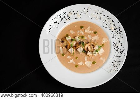 Creamy Soup With Mushrooms And Croutons On Black Table