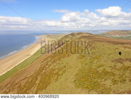 Paragliders Flying Above Rhossili Beach In Wales