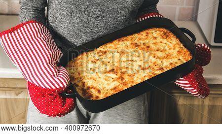Cottage Cheese Casserole On A Baking Sheet. Homemade Pie In Hands. Kitchen Mittens. Dessert