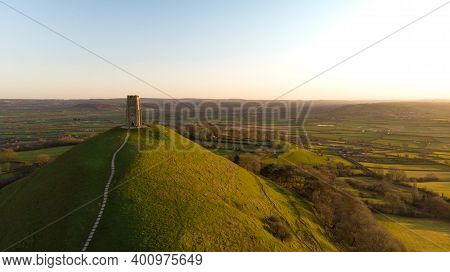 Aerial View Of The Early Morning Sunrise Over Glastonbury Tor With Somerset Fields Below.