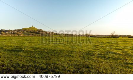 Early Morning View Of Glastonbury Tor In A Somerset Field At Golden Hour.