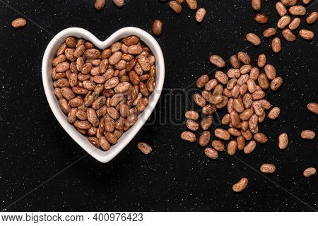Pinto Beans Or Speckled Beans In A Heart Shaped Bowl Background And Texture. Top View.