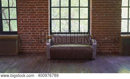 Brownish Brick Wall With Leather Sofa. Background Photo With Copy Space For Text. Claret Leather Sof