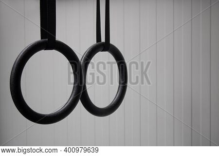 Detail Of A Set Of Black Gymnastic Rings Or Steady Rings Hanging In Home Gym Over A White Wall On Th