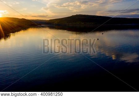 Aerial View Of Fisherman At The Boat On Golden Sunset River. Silhouette Of Fishermen With His Boat,