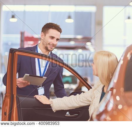 Beautiful Young Woman Is Talking To Handsome Car Dealership Worker While Choosing A Car In Dealershi