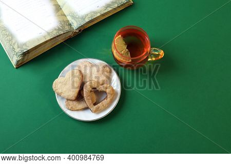 A Cup Of Tea With Lemon, A Heart Cookie On A Saucer, An Unfolded Book On A Green Background, A Top V