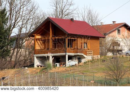 Modern Newly Built Wooden Log House With Big Open Porch In Front And New Roof Tiles On Side Of Small