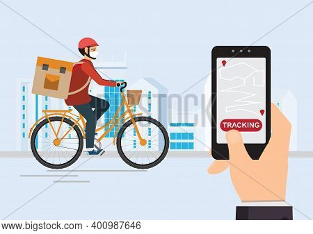 Courier On A Bike With Parcel Box On The Back Tracking An Order Using His Smartphone, City Street In