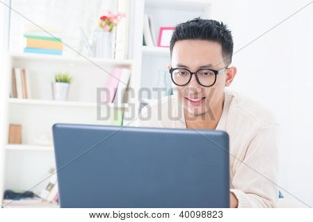 Southeast Asian male using notebook online at home, indoor living lifestyle