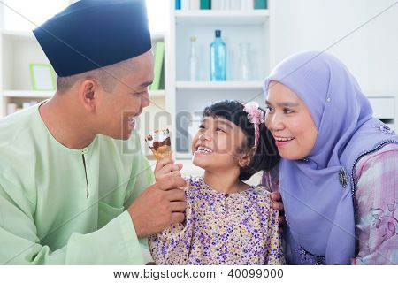 Southeast Asian girl feeding ice cream to father. Malay Muslim family lifestyle