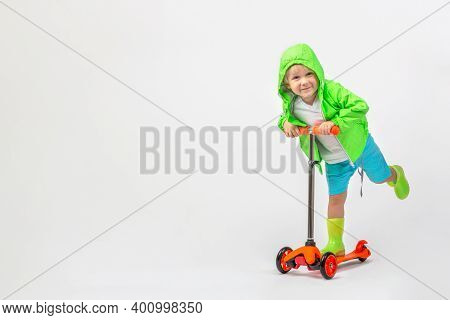 Cheerful Child Kid In Bright Green Jacket With Hood And Rubber Boots Rides Scooter On White Backgrou