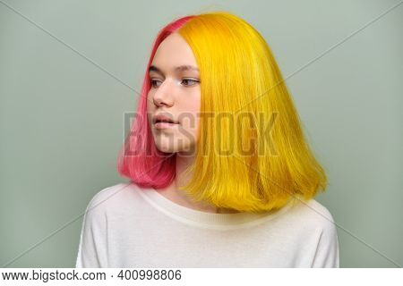 Headshot Of Fashionable Beautiful Teen Girl With Trendy Dyed Hair Against Green Background. Teenager