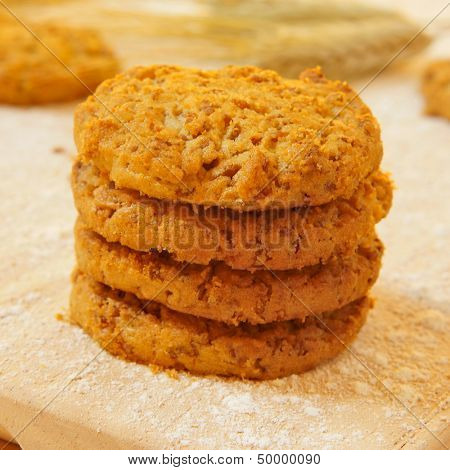 closeup of some bran flake cookies on a wooden worktop peppered with flour and some wheat ears in the background