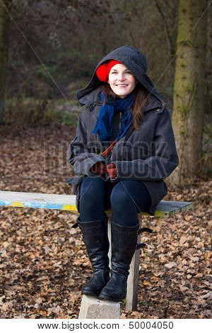 Young Happy Woman Sitting On A Bench During A Cold Winter Day