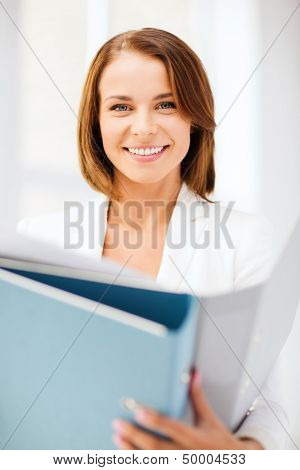 business concept - businesswoman with folders in office