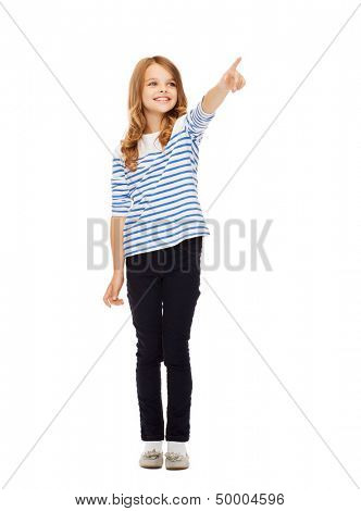 education, school and imaginary screen concept - cute little girl pointing in the air or imaginary screen