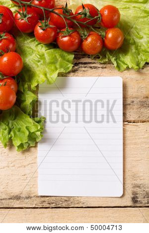 food and cooking concept - cherry tomatoes on wood background with white blank paper