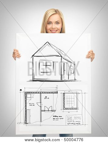 real estate, property, business and accomodation concept - woman holding picture with house and blueprint