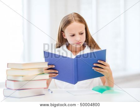 education and school concept - little student girl studying and reading book at school