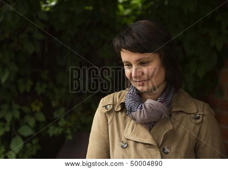 Thoughtful mature woman in autumn park. Real people series.