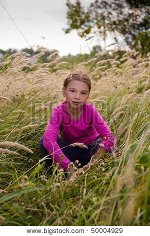 Baby girl sitting in a meadow.
