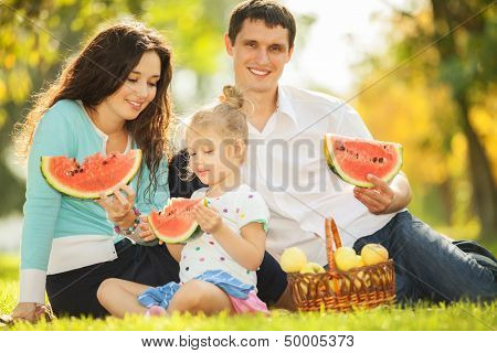 Happy family having a picnic in the green garden