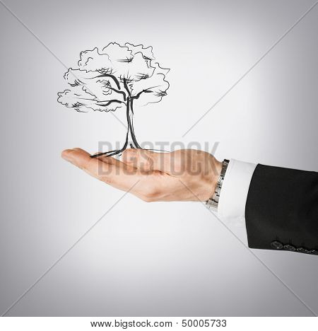 environment, ecology and nature protection concept - man with small tree in his hand