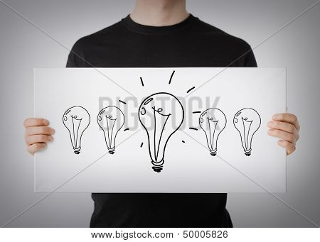 energy and environment concept - man showing picture with light bulbs