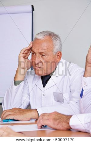 Pensive senior doctor thinking in a team meeting