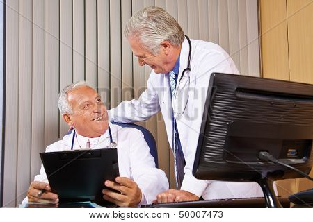 Two smiling senior physicians talking in a hospital office