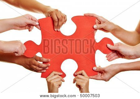 Many hands holding a big red jigsaw puzzle piece