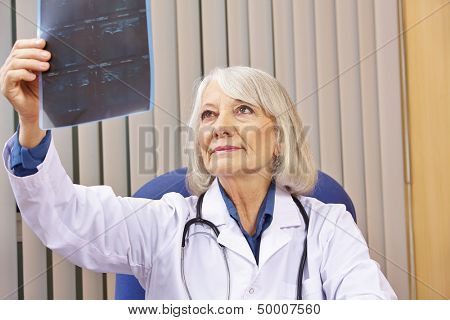 Senior doctor evaluating x-ray image in her office
