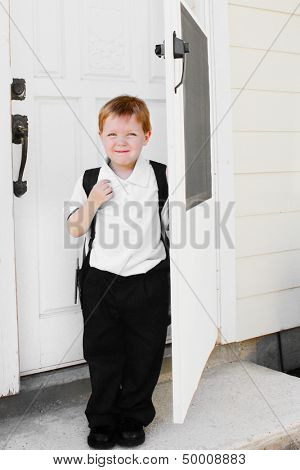Little boy ready for school stands by the door of the house