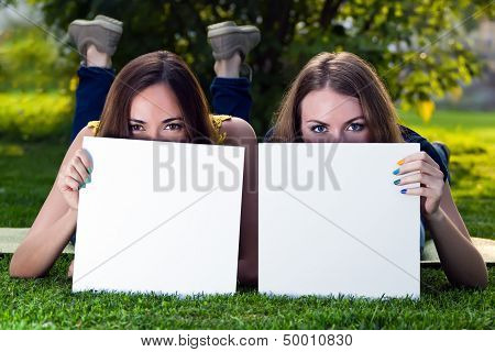 Happy Young Girls Holding White Blank Papers Against Background Of Summer Green Park