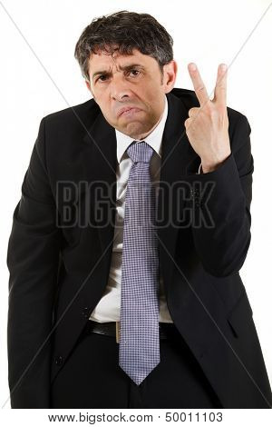 Businessman making a rude derogatory v-sign gesture with his hand while grimacing and frowning at the camera, three quarter portrait on white