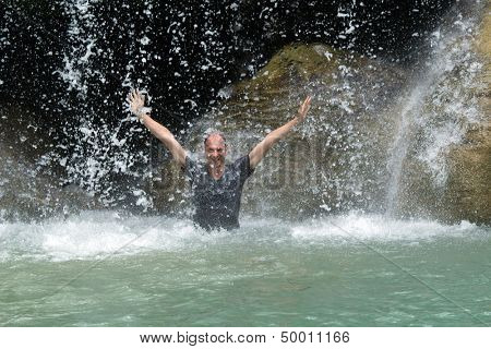Man relaxing under tropical Erawan waterfall, Thailand