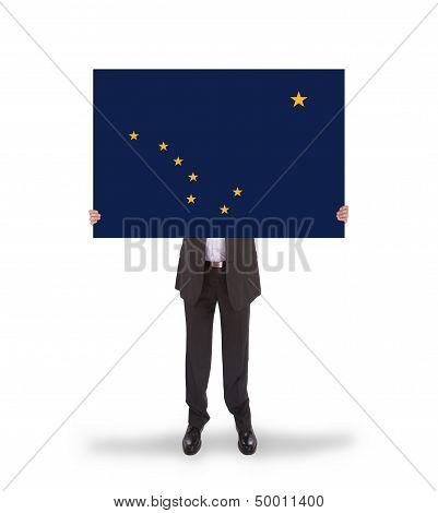 Smiling Businessman Holding A Big Card, Flag Of Alaska