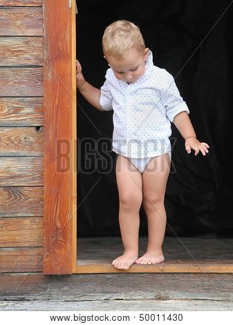 Little boy in the doorway to an rural house.