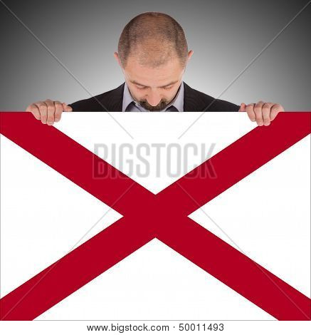 Smiling Businessman Holding A Big Card, Flag Of Alabama