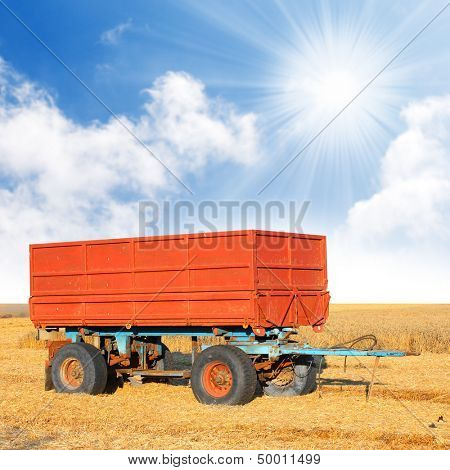 A red trailer on wheat field.