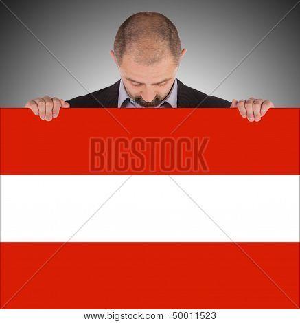 Smiling Businessman Holding A Big Card, Flag Of Austria