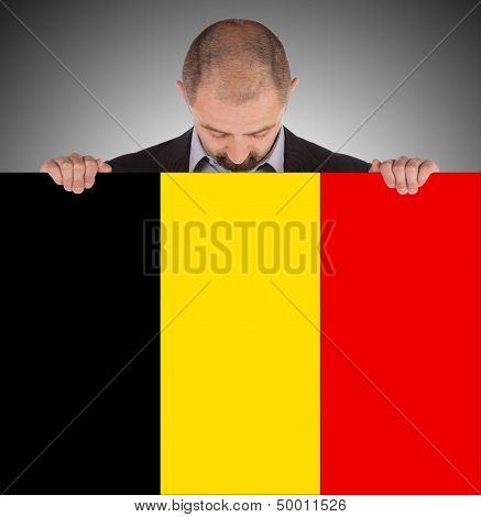 Smiling Businessman Holding A Big Card, Flag Of Belgium