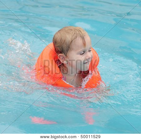 Little child in the life jacket floating. Insurance concept.