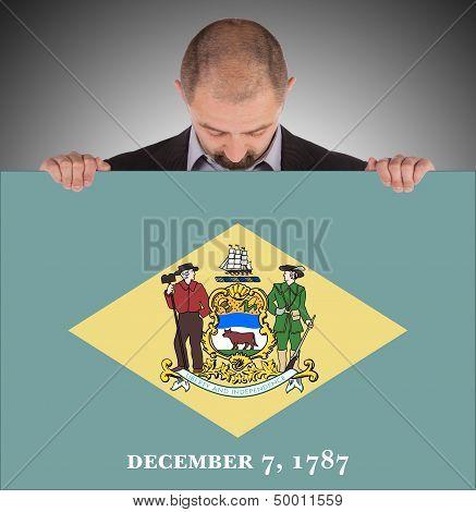 Smiling Businessman Holding A Big Card, Flag Of Delaware