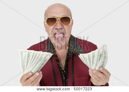 Portrait of excited senior man showing US banknotes with mouth open against gray background