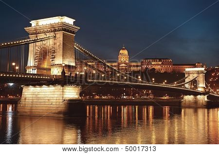 Dusk cityscape of the Chain bridge across the river Danube with the Buda castle in the background in the Hungarian capital Budapest poster