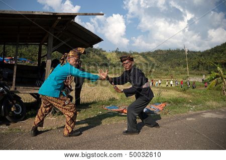 SUMATERA - AUGUST 24: Two elderly 'silat' martial arts exponents perform for guests in a welcome ceremony at the bull race festival on August 24, 2013 in Batu Sangkar, West Sumatera, Indonesia.